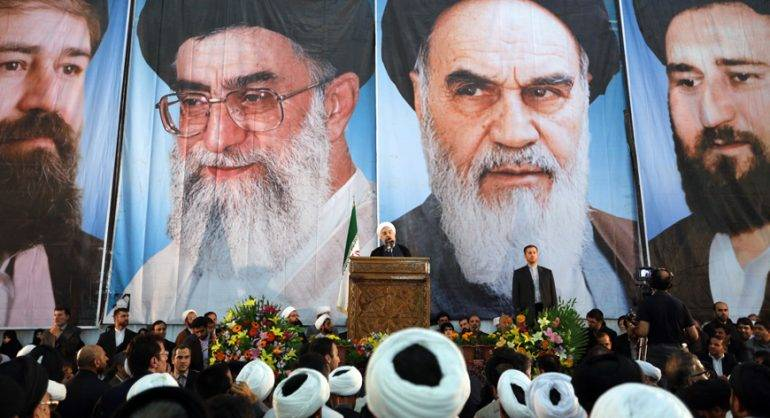 Iranian President Hassan Rouhani delivers a speech under portraits of Iran's supreme leader, Ayatollah Ali Khamenei (Center L) and Iran's founder of the Islamic Republic, Ayatollah Ruhollah Khomeini (Center R), on the eve of the 25th anniversary of the Islamic revolutionary leader Ayatollah Ruhollah Khomeini's death, at his mausoleum in a suburb of Tehran